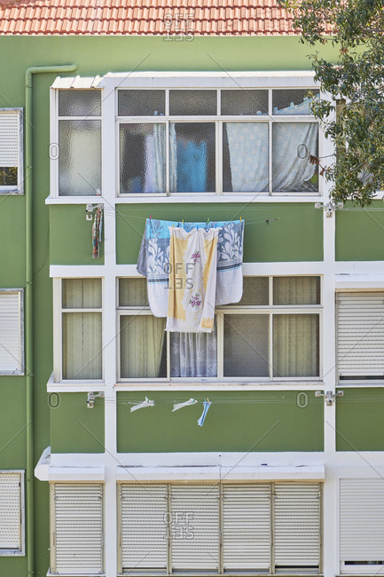 Lisbon, Portugal - September 30, 2019: Green facade of apartment building with laundry hanging outside windows