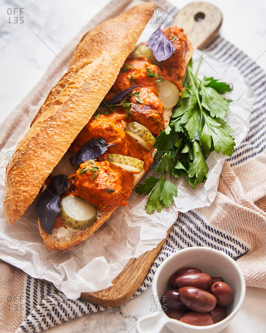 Close up of a meatball sub with pickles and olives on the side