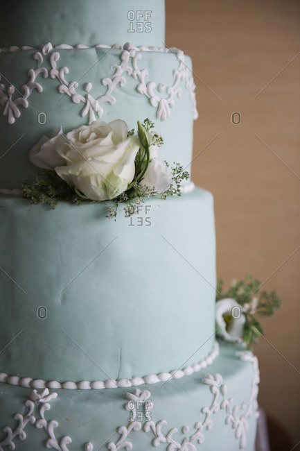 Detail of a beautiful blue pastel wedding cake with white roses