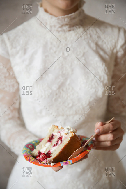 Bride holding a slice of her wedding cake