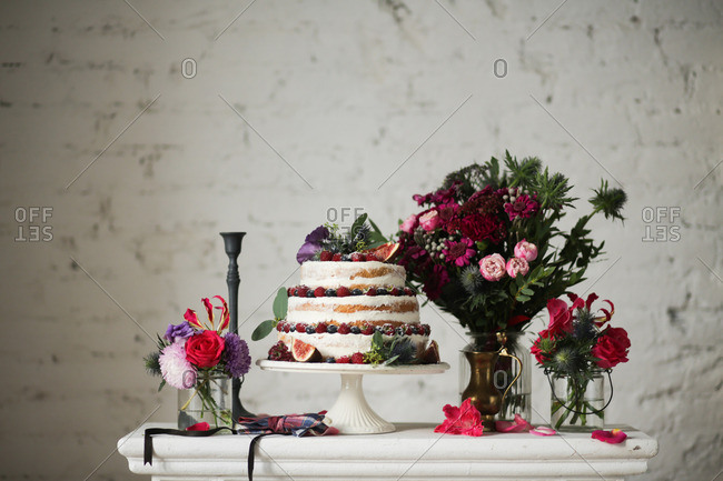 Beautiful wedding cake with fruit on a table surrounded by flowers