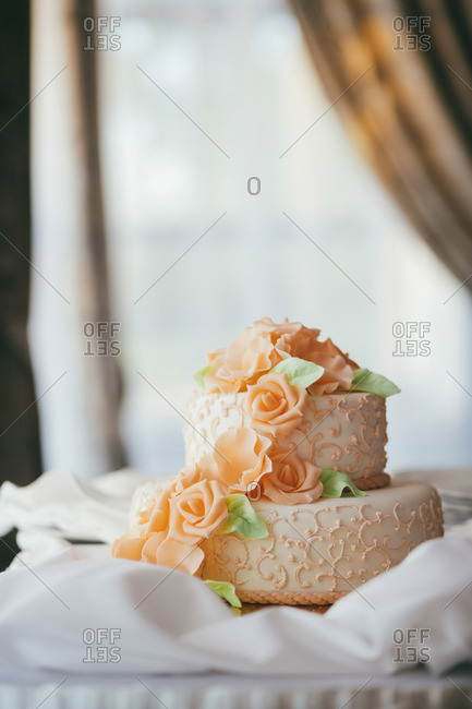 Detail of a beautiful wedding cake with orange icing roses