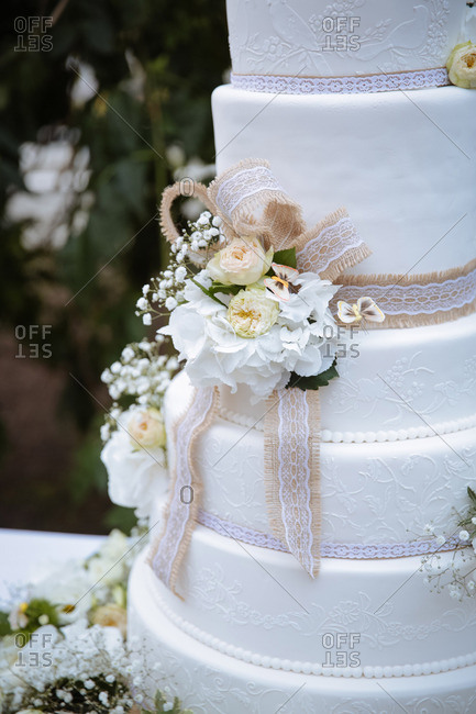 Tall wedding cake with burlap, lace and flowers