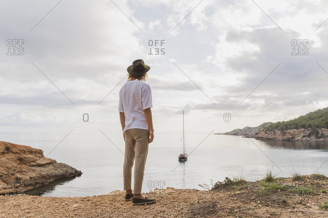 Back view of young man standing in front of the sea looking at view- Ibiza- Balearic Islands- Spain