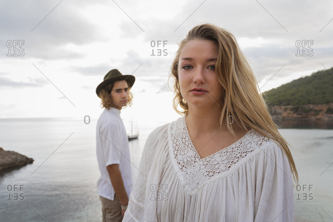 Portrait of young woman in front of the sea with boyfriend in the background- Ibiza- Balearic Islands- Spain