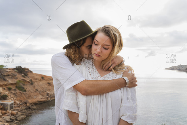 Young couple in love standing in front of the sea- Ibiza- Balearic Islands- Spain