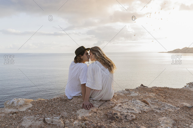 Back view of young couple in love sitting on rock in front of the sea- Ibiza- Balearic Islands- Spain