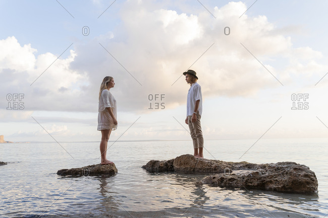 Young couple standing on rocks in front of the sea- Ibiza- Balearic Islands- Spain
