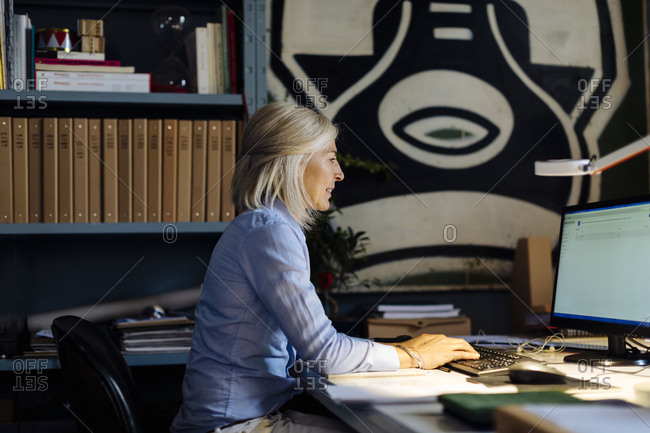 Mature woman working in architect's office- using PC