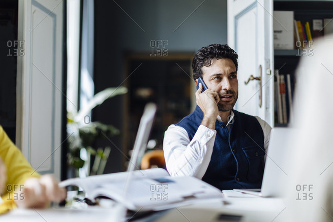 Mid adult man sitting in his office- talking on the phone