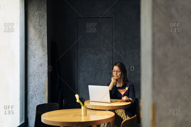 Woman using laptop- drinking cocktail