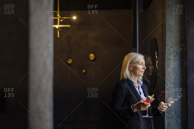 Mature businesswoman taking after work cocktail- using smartphone