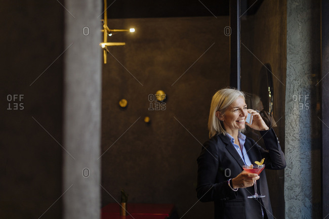 Mature businesswoman taking after work cocktail- talking on the phone