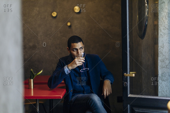Young man relaxing with an after work cocktail