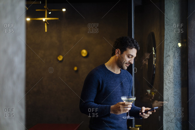 Businessman in stylish office- taking after work cocktail- using smartphone