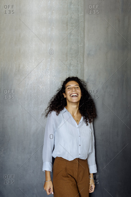 Portrait of a laughing young businesswoman standing in front of a grey wall