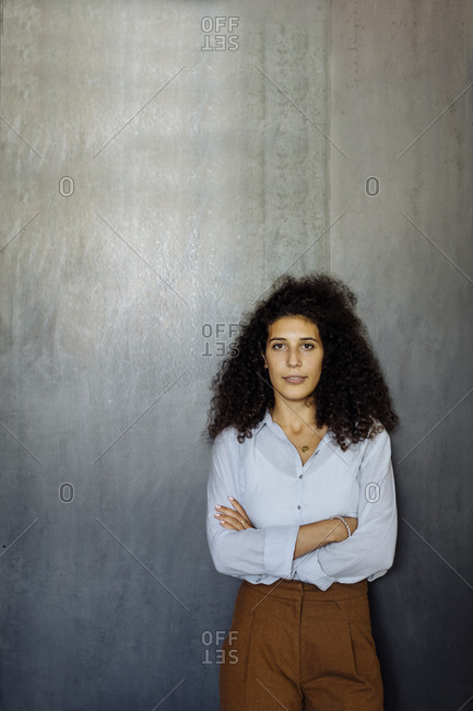 Portrait of a confident young businesswoman standing in front of a grey wall