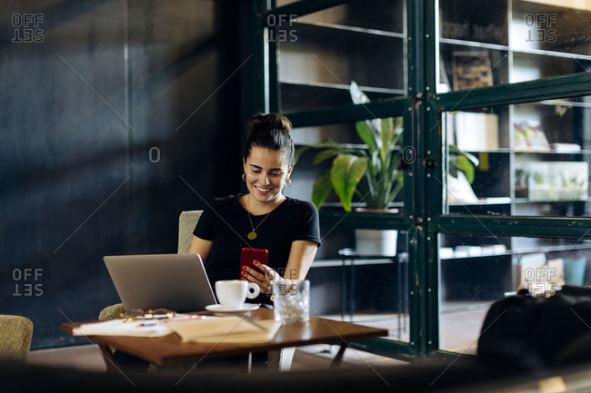 Casual young businesswoman with laptop and smartphone in loft office