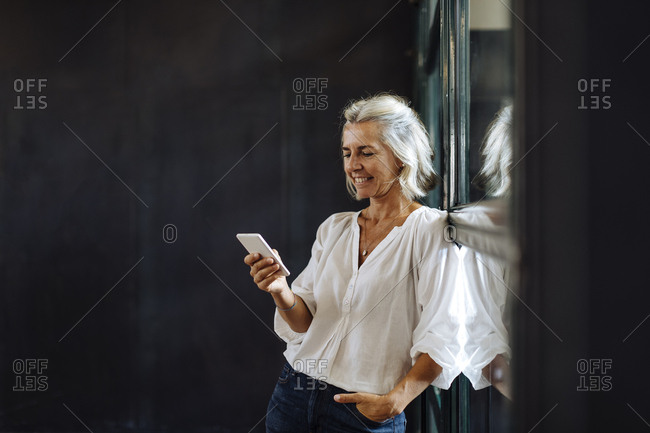 Smiling casual mature businesswoman using smartphone at the window in loft office