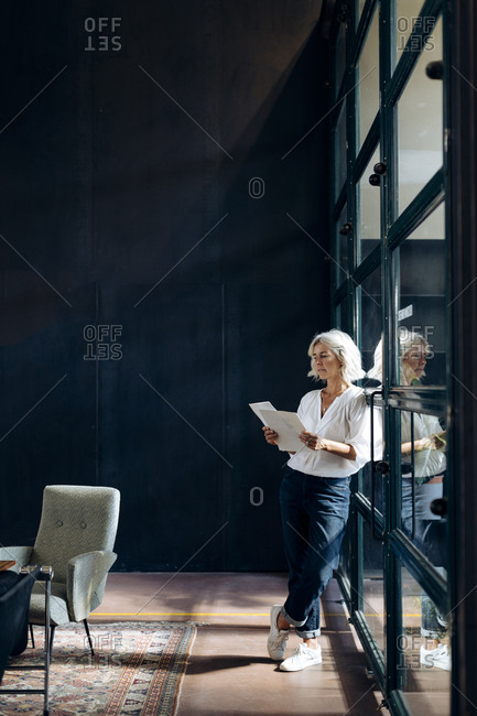 Casual mature businesswoman reviewing papers in loft office