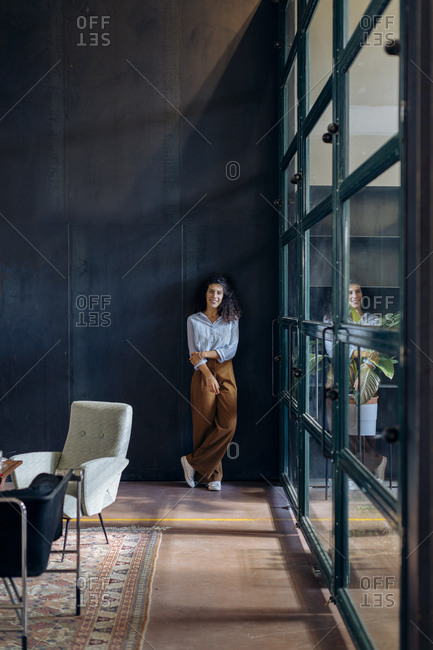 Portrait of young businesswoman standing at the window in loft office