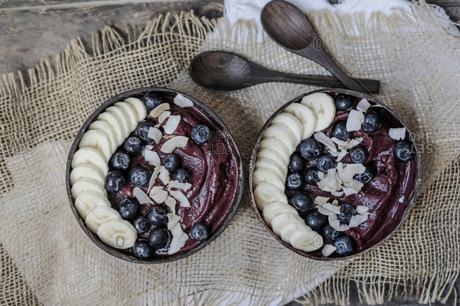 Directly above shot of ice cream served with banana slices and blueberries in bowls on table