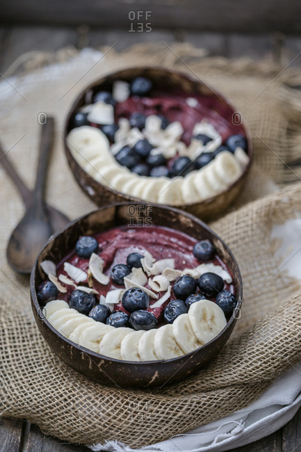 High angle view of ice cream served with banana slices and blueberries in bowls on table