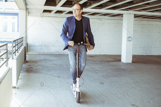 Mature businessman riding e-scooter in parking garage
