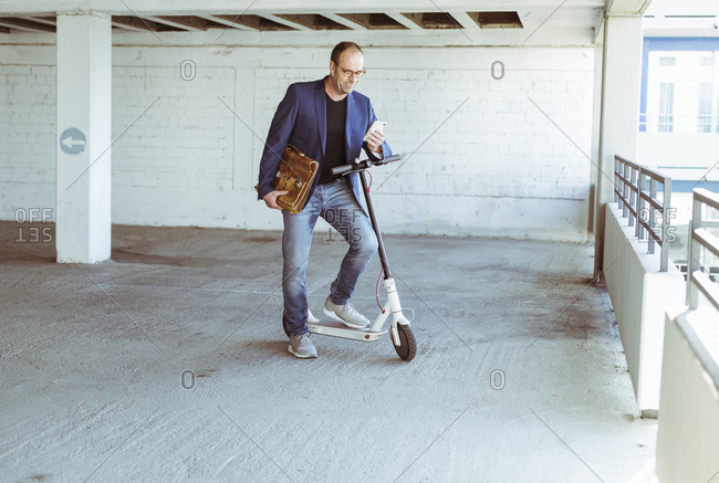 Mature businessman with e-scooter and smartphone in parking garage
