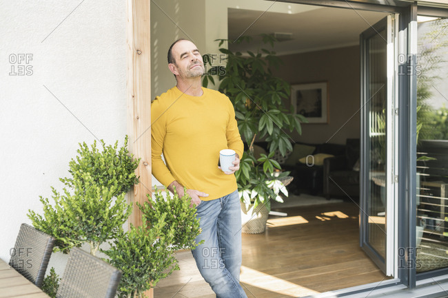 Mature man with closed eyes standing at terrace door at home with coffee cup