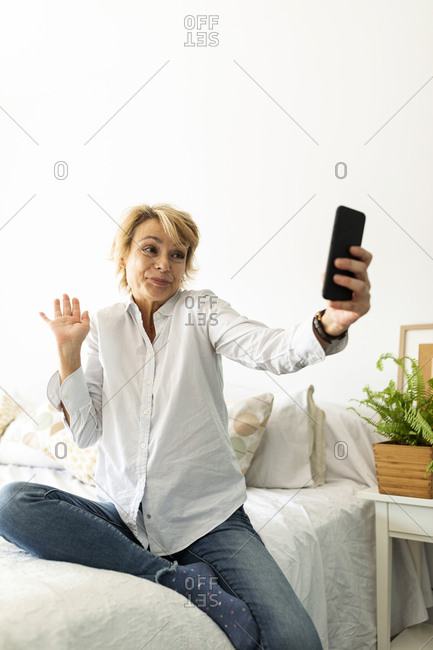 Mature woman sitting on bed at home taking a selfie