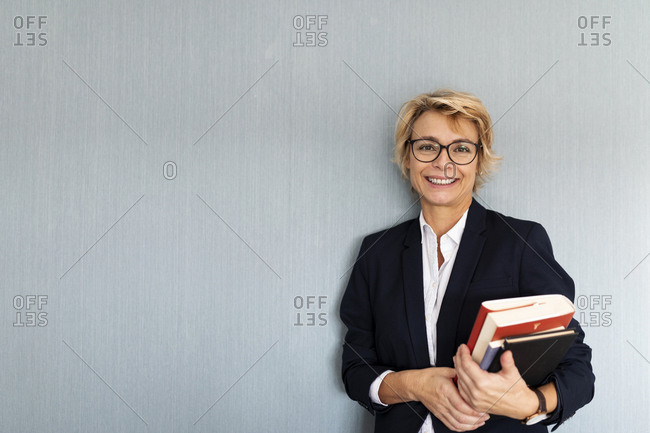 Portrait of mature businesswoman standing at a wall holding stack of books