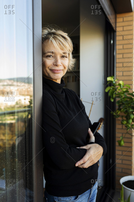 Portrait of mature woman leaning at the window