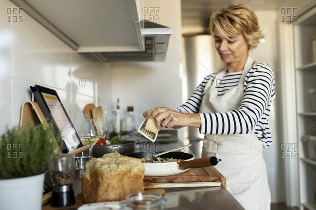 Mature woman with tablet cooking pasta dish in kitchen at home