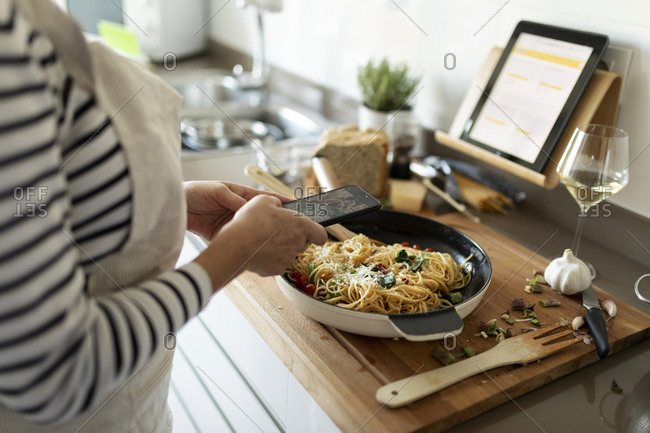 Close-up of woman taking smartphone picture of her pasta dish in kitchen at home