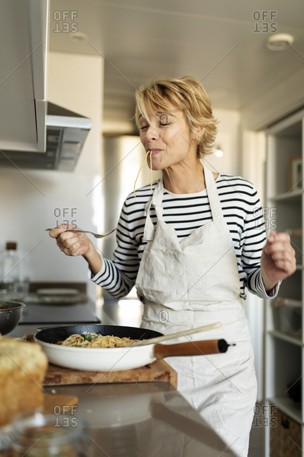 Mature woman tasting homemade pasta dish in kitchen at home