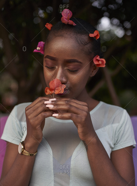 Portrait of young woman smelling a flower