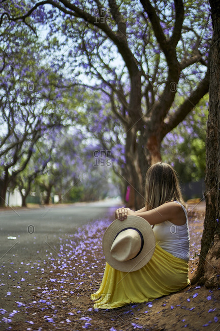 Woman leaning on a tree at a street with jacaranda trees in bloom- Pretoria- South Africa
