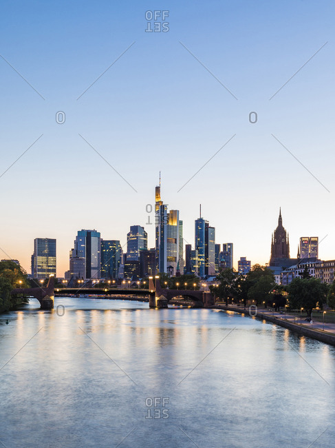 July 3, 2019: Scenic view of river in illuminated city against clear sky during sunset at Frankfurt- Germany