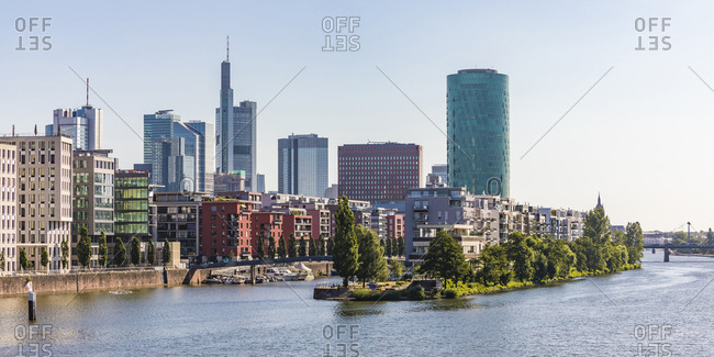 July 4, 2019: Buildings and Westhafen Tower by river against clear sky in Frankfurt- Germany