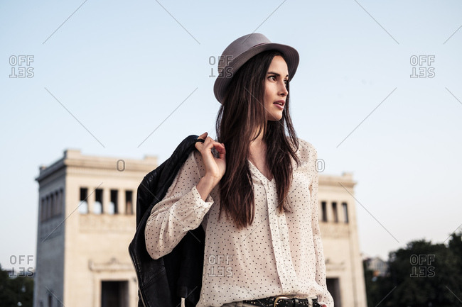 Portrait of young woman with long brown hair wearing hat looking at distance- Munich- Germany