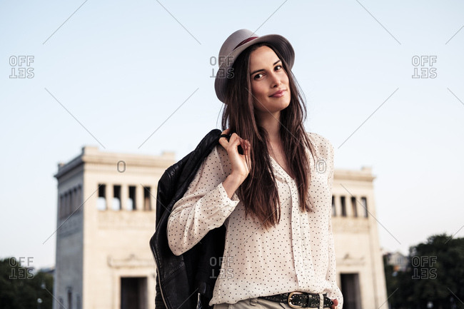Portrait of young woman with long brown hair wearing hat- Munich- Germany