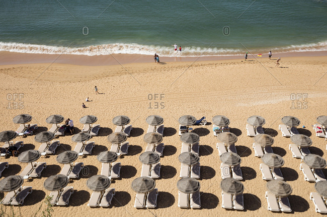May 28, 2019: High angle view of lounge chairs and parasols at sandy beach during summer- Albufeira- Algarve- Portugal