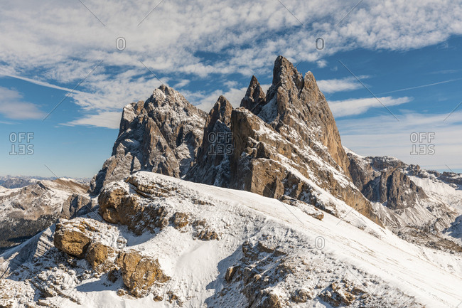 Idyllic shot of snow covered Seceda peak and mountains against sky- Italy