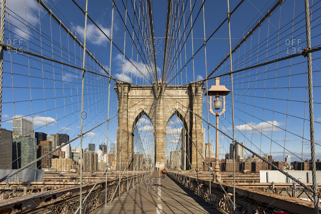 Diminishing perspective of Brooklyn Bridge against blue sky in New York City- USA