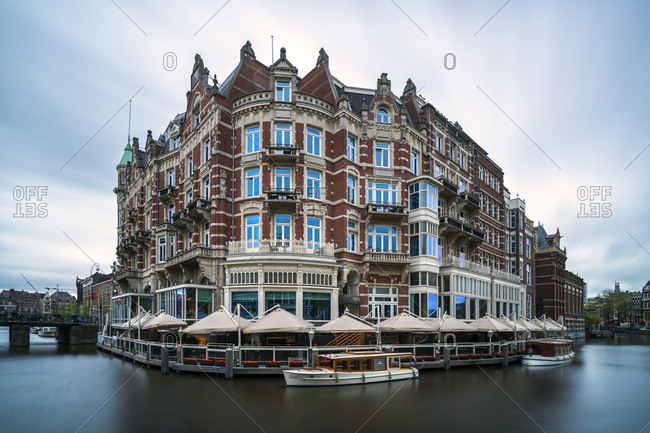 May 19, 2017: Netherlands- Amsterdam- Cafe canopies surrounding waterfront buildings