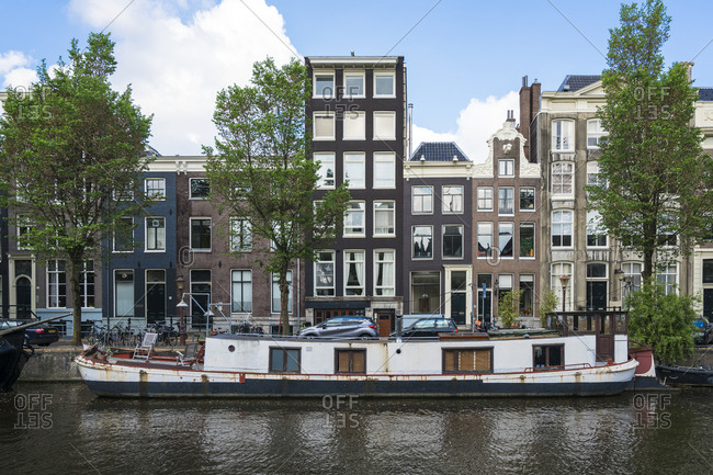 May 20, 2017: Netherlands- Amsterdam- Barge moored along edge of city canal with row of houses in background