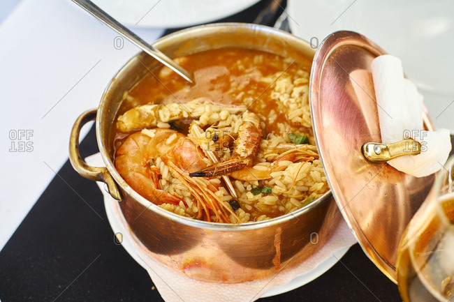 Saffron rice with seafood in a copper pot. Restaurant food for two people. Top view. Portuguese cuisine