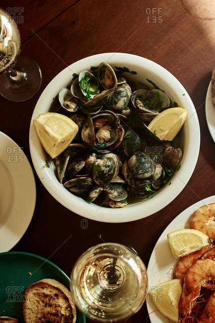 Cooked clams and shrimp with white wine, butter, lemon and parsley. Summer lunch at home. Portuguese cuisine