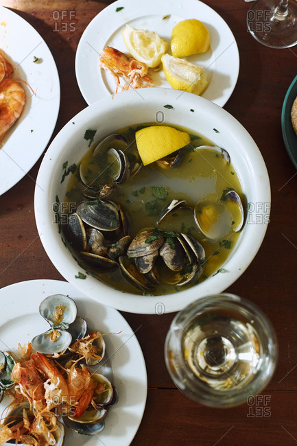 Cooked clams and shrimp with white wine, butter, lemon and parsley. Summer lunch at home. Portuguese cuisine. Top view